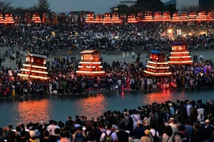 Saijo, Japan. Illuminated floats called dainjiri cross the Kamogawa river towards the Isono shrine at the climax of an autumn festival