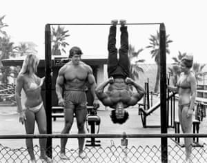 Schwarzenegger watches on as Franco Columbu hangs from a bar in the film Pumping Iron.