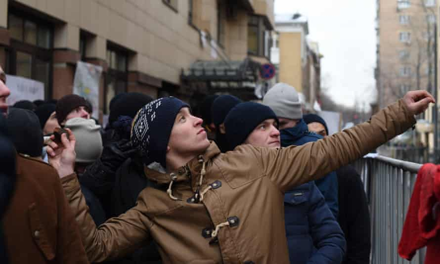 A protester throws a stone towards Turkey embassy in Moscow during a protest against the downing of a Russian warplane by Turkey on Wednesday.