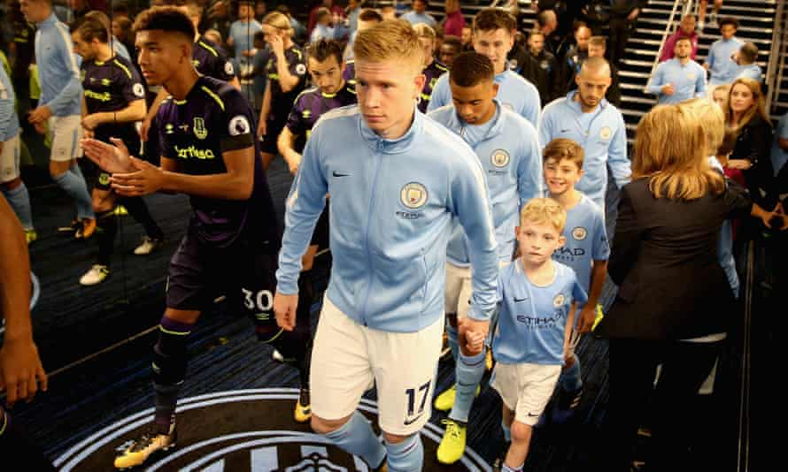 Manchester City's Kevin De Bruyne, centre, and Everton's Mason Holgate, left, head through the Etihad Stadium's tunnel along with their team-mates