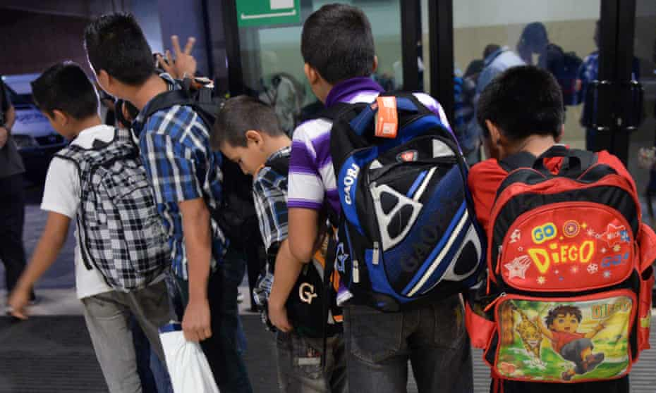 Guatemalan children caught in Mexico while trying to migrate into the US, queue before climbing into a minibus at Aurora international airport in Guatemala City.