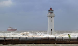 Men walk past Perch Rock lighthouse as a ship enters the mouth of the River Mersey during a storm at New Brighton near Liverpool.