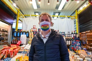 A market trader wears a rainbow face mask with the message 'We will all succeed' in Trionfale, Rome