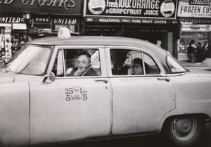 Taxicab driver at the wheel with two passengers, NYC, 1956.