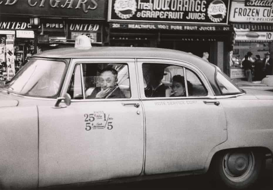 Taxicab driver at the wheel with two passengers, N.Y.C. 1956 by Diane Arbus.