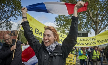 A Gilet Jaune protestor holds a French Tricolor flag.