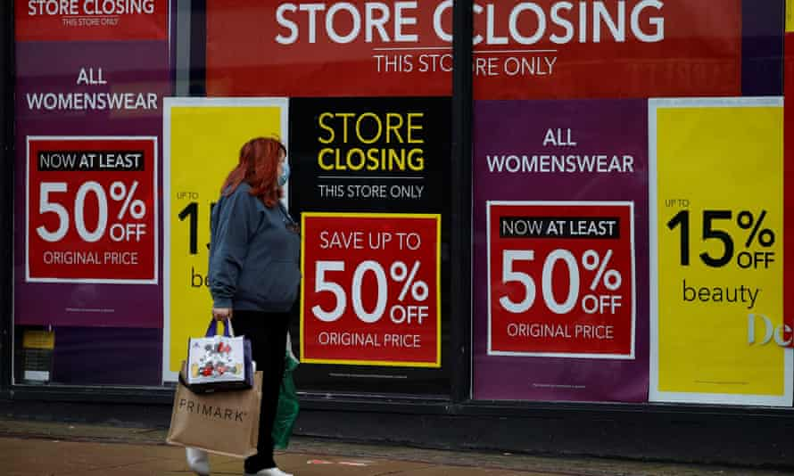 Woman walks past sale signs