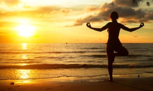 Woman practicing yoga on the beach during the sunset