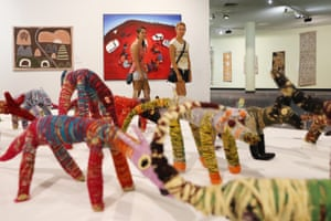 Visitors at the Museum and Art Gallery of the Northern Territory browse works including a painting by Jody Broun titled White Fellas Came to Talk Bout Land (centre, rear) and mixed-media sculptures by Tjanpi Desert Weavers titled Big Mob of Tjanpi Dogs (foreground)