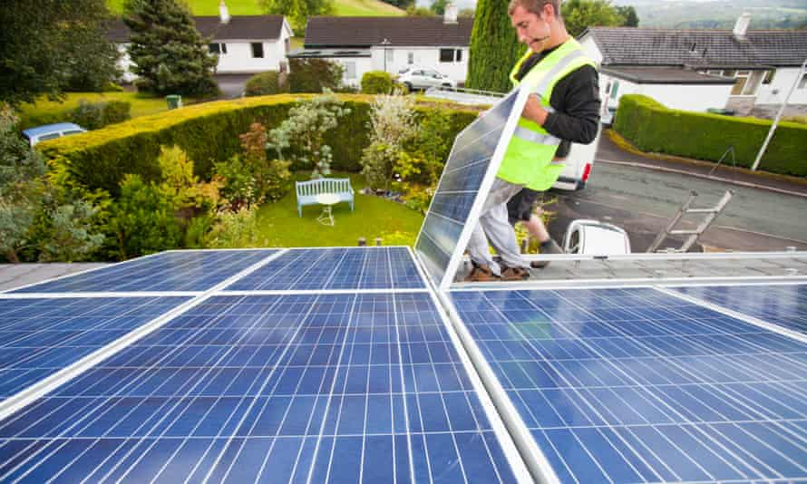Workers installing solar panels on a house roof in Ambleside, UK.