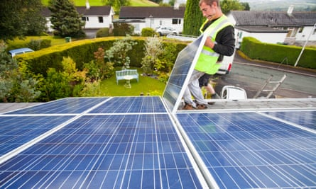 Workers installing solar electric panels on a house roof in Ambleside, UK. The solar industry argues that 27,000 jobs are at risk from the proposed cuts.