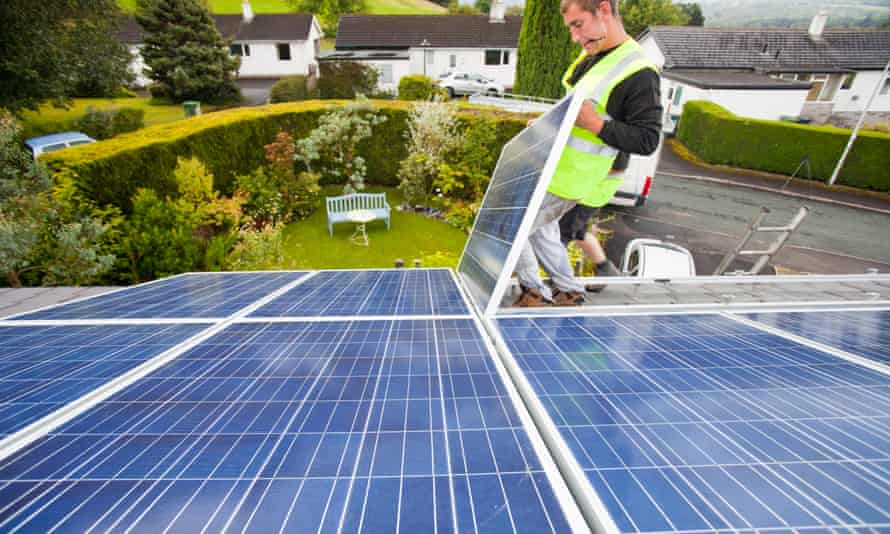 Workers installing solar electric panels on a house roof in Ambleside, UK