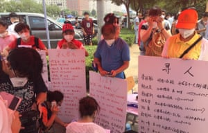 Relatives of Tianjin residents missing after the blasts hold up information about their loved ones.
