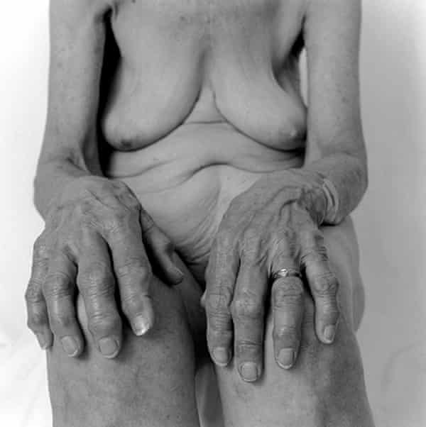 Photo of naked elderly woman with her hands on her knees
