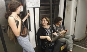 Mayor of Barcelona Ada Colau speaks with a woman as she uses the underground to the city centre.