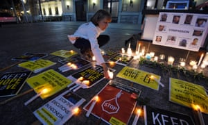 A woman lights a candle during a vigil for Australians Myuran Sukamaran and Andrew Chan in Brisbane.