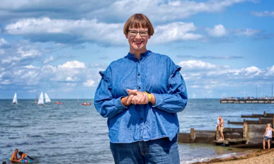 Katherine May standing on a beach with a few sailing boats and the sea behind her