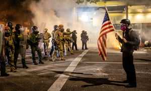 A protester holds up an American flag as federal agents make an attempt to clear a crowd in Portland, Oregon Wednesday night.