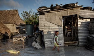 A young girl wades through the incoming sea water that flooded her house and village in Kiribati.