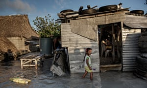 A young girl wades through the seawater that flooded her house and village