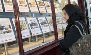 A first-time buyer looking at properties for sale in an estate agent's window in London