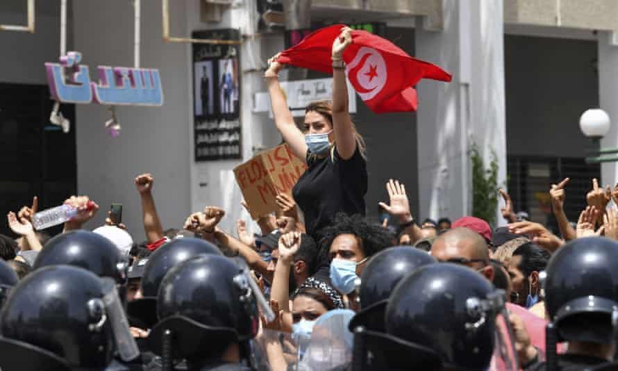 A Tunisian protester lifts a national flag at an anti-government rally