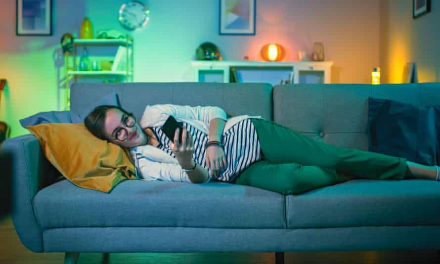 Woman lying on a couch with her mobile phone