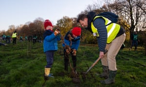 David Elliott, Trees for Cities chief executive, plants a seedling with his children.
