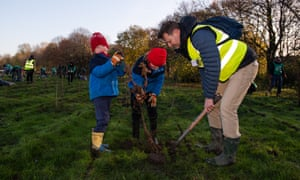 David Elliott, chief executive of Trees for Cities, planting trees with his children Casper and Rafael.
