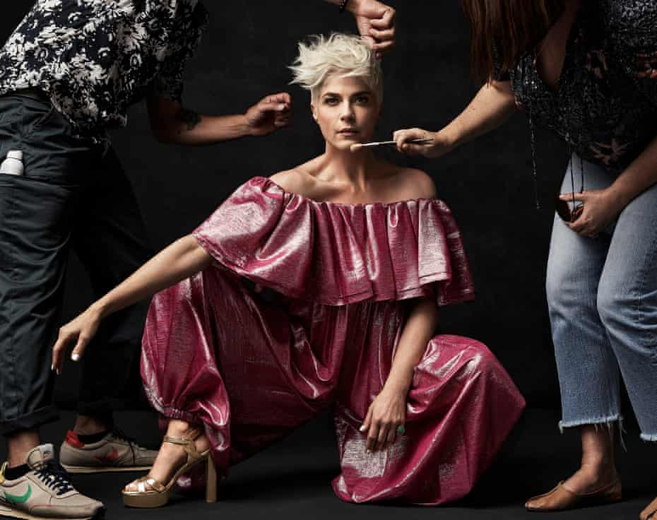 Selma wears jumpsuit by Alexandre Vauthier and shoes by Stuart Weitzman. Shown with make-up artist and hair stylist either side of her making finishing touches
