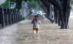A pedestrian walks on waterlogged streets in Fuzhou, China. Typhoon Megi has brought torrential rains to the province.