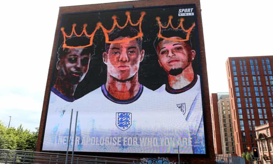 A digital mural of Bukayo Saka, Marcus Rashford and Jadon Sancho at Trafford Park, Manchester.