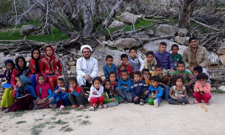 Esmail Azarinejad, an Iranian cleric, is surrounded by children who he supplies with books.