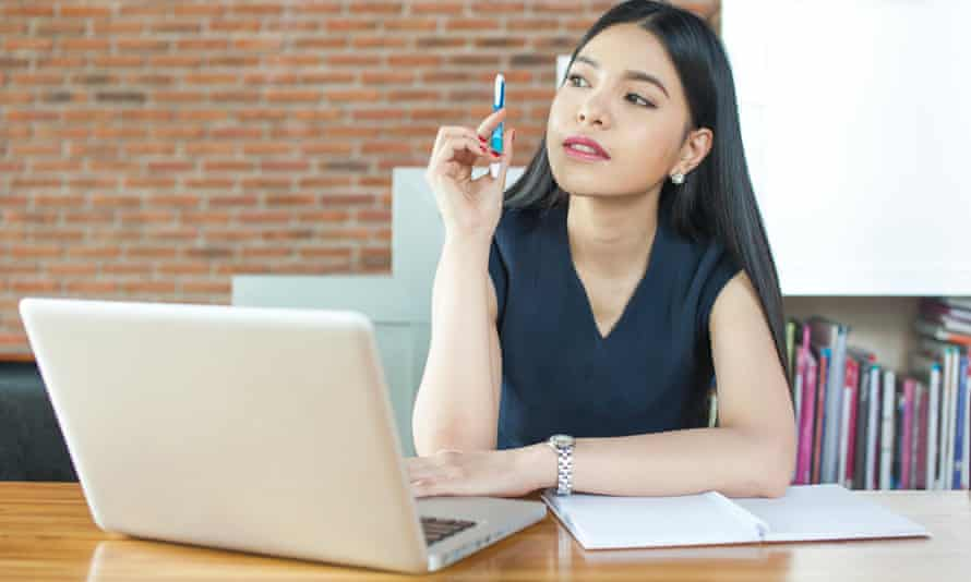 woman looking at computer with notepad