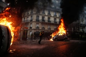 Protesters walk past burning cars during clashes with riot police on the sidelines of a protest by yellow vests gilets jaunes (yellow vests) against rising oil prices and living costs.