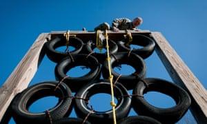 A man climbs over a tire tower