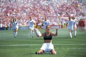 Brandi Chastain celebrates after scoring the winning penalty in the shootout against China as her teammates rush to congratulate her.