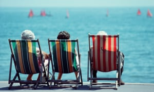 Three older women sitting in deckchairs at the seaside
