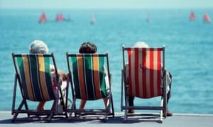 Three retired ladies sitting in deckchairs on seaside promenade.