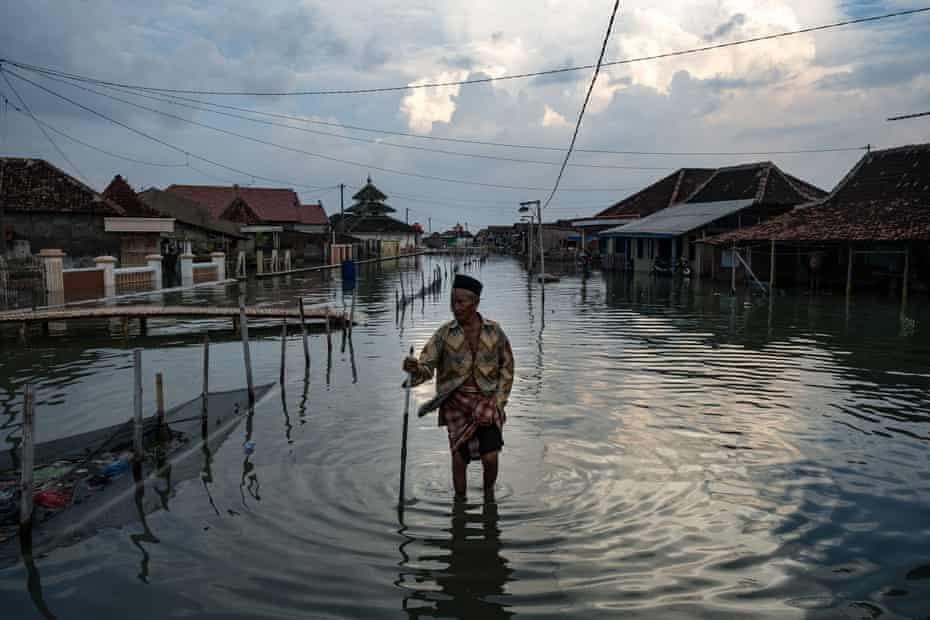 A resident of Demak district in central Java makes his way through the inundated streets of his village.