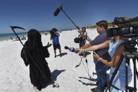 Daniel Uhlfelder, dressed as the Grim Reaper, speaks to reporters at the newly reopened beach in Destin, Florida, on 1 May.