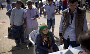 A woman waits to complete her registration procedure by the police at a new registration centre held in a stadium on the Greek island of Lesbos.