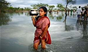 A woman wades through flood waters in the aftermath of Cyclone Aila in Harinagar, Satkhira, Bangladesh in May 2009