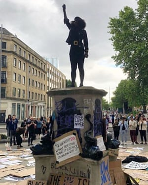 A triumphant call for action … Jen Reid standing on the Colston plinth in Bristol, just after the statue was toppled.