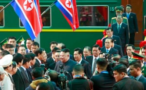 Kim Jong-un, followed by members of his delegation, is welcomed at Đồng Đăng railway station