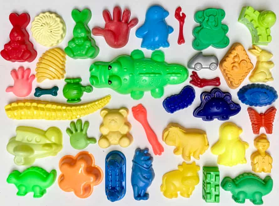 Colourful plastic toys found by a beachcomber laid out as if they were in a display case in a museum