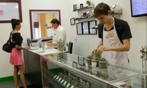 Employees at a marijuana dispensary help a customer choose her products, in Portland, Oregon.