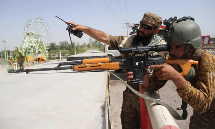 Afghan security officials guarding at a roadside checkpoint in Herat, Afghanistan