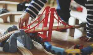 Boy playing with trains on track on floor.