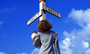 Back view of a business woman holding baby and standing at a crossroads with a sign pointing to 'family' in one direction and 'career' in the other, blue sky behind